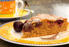 Cherry Almond Cake With Fresh Cherries on Bright Plate. Cherry almond cake with fresh cherries, fork,  bright yellow plate and orange cup Stock Photos