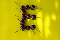 Cherry berries on a bright yellow background in the form of the letter E with sun highlights royalty free stock images