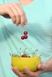 Cherry Berries in den Mannhänden und -platte Stockbilder
