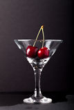 Cherry berries in a martini glass on black background Royalty Free Stock Photos