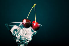 Cherry berries in a martini glass on black background. Toned Royalty Free Stock Images