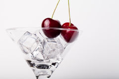 Cherry berries in a martini glass on white background Royalty Free Stock Images
