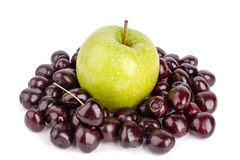 Cherry berries and one big green apple on white background isolated close up macro stock photo