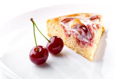 Cherry berries and piece of cream fruit pie on white plate close-up. Cherry berries with sprig and piece of cream fruit pie on white plate close-up stock images