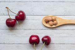 Cherry berries and a spoon on a wooden background top view, close-up Royalty Free Stock Photography