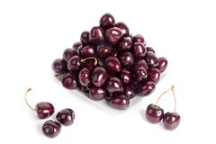 Cherry berries in water drops on white plate white background isolated close up macro stock image