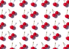 Cherry berries on the white background on the noon sun. Summer food pattern. Top view stock image