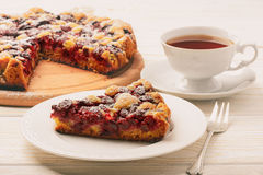 Cherry biscuit pie and cup of tea on white wooden background. Royalty Free Stock Image