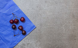 Cherry on blue paper and gray background from stone Stock Images