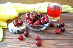 Cherry in a bowl and compote on the table Stock Image