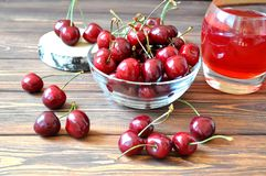 Cherry in a bowl and compote on the table Stock Photos