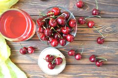 Cherry in a bowl and compote on a wooden table Royalty Free Stock Photos