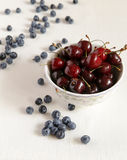 Cherry in a bowl on a table, lies bilberry nearby. A cloth from flax Stock Image