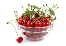 A cherry with a branch lies near a dish Royalty Free Stock Image