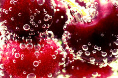 Cherry bubbles. Close up of cherries immersed in mineral water royalty free stock photo