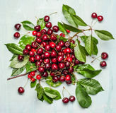Cherry bunch with with berries and green leaves and branch on wooden background Royalty Free Stock Photos