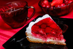 Cherry cake. On a black plate, on a red background Royalty Free Stock Image