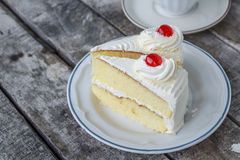 Cherry on cake slice. Cake with Maraschino cherry isolated stock photo
