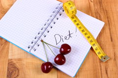 Cherry and centimeter with notebook, slimming and healthy food Royalty Free Stock Image