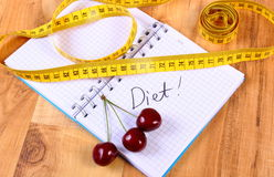 Cherry and centimeter with notebook, slimming and healthy food Royalty Free Stock Photo