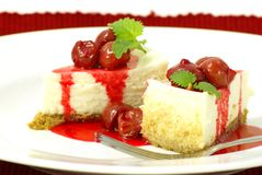 Cherry Cheesecake. New York style cheese cake slices with rich cherry sauce topping and mint (lemon balm) leaf garnish Stock Photography