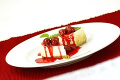 Cherry Cheesecake. New York style cheese cake slices with rich cherry sauce topping and mint (lemon balm) leaf garnish Royalty Free Stock Image