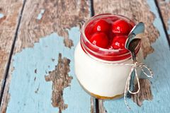 Cherry cheesecake in a mason jar with spoon Royalty Free Stock Photos