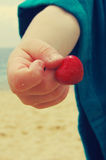 Cherry in the child's hands. Cherry in the form of heart. Stock Photo