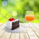 Cherry chocolate cake and Orange juice setting on wood table Stock Image