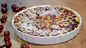Cherry Clafoutis med pudrat socker i bakningdisk stock video