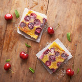 Cherry clafoutis pie portions on wooden table Stock Image