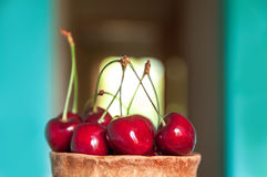 Cherry in a clay cup. On the background of a window Royalty Free Stock Image