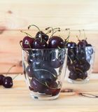 cherry in clear glasses on a wooden background Royalty Free Stock Photo