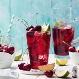 Cherry cola, limeade, lemonade, cocktail in a tall glass on a white, turquoise background Stock Photos
