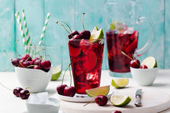 Cherry cola, limeade, lemonade, cocktail in a tall glass on a white, turquoise background. Copy space Royalty Free Stock Photos