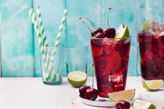 Cherry cola, limeade, lemonade, cocktail in a tall glass on a white, turquoise background. Copy space Stock Photo
