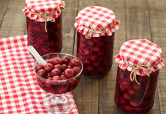 Cherry compote. Homemade winter stores, sweet ripe cherries in vintage jars Stock Photo