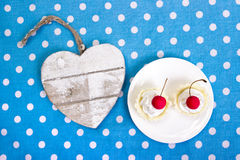 Cherry cookies and heart. Cherry cookies on white plate with wooden heart Royalty Free Stock Photo