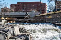 Cherry Creek Bike Path at Colfax Ave. Woman commuting on bike on Cherry Creek Bicycle Path bridge over the creek royalty free stock images