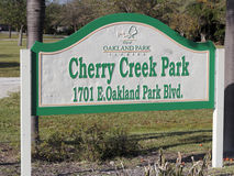 Cherry Creek Park Sign Outside. Oakland Park, FL, USA - March 10 2017: Green, white and yellow Cherry Creek Park sign outside on a sunny day. Cherry Creek Park Royalty Free Stock Image