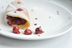 Cherry Crepe Dish on Round White Ceramic Plate stock image
