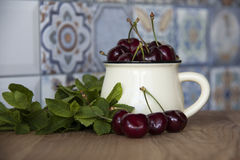 Cherry in cup on wooden table. Cherry in cup on wood Royalty Free Stock Images