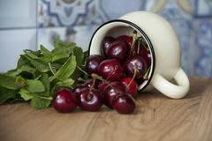 Cherry in cup on wooden table. Cherry in cup on wood Royalty Free Stock Image