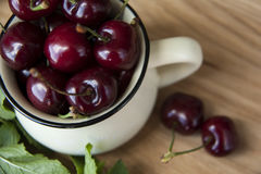 Cherry in cup on wooden table. Cherry in cup on wood Royalty Free Stock Photos