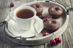 Cherry cupcakes and cup of tea on a wooden tray Stock Images