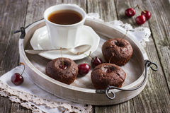 Cherry cupcakes and cup of tea on a wooden tray Royalty Free Stock Photography
