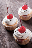 Cherry cupcakes. Three cherry cupcakes, on wooden table stock images