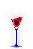 Cherry drop into red wine with splash Royalty Free Stock Image