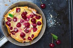 Cherry Dutch Baby, Puff German Pancake on Vintage Pans and Dark Background, Homemade Summer Dessert. Cherry Dutch Baby, Puff German Pancake on Vintage Pans and royalty free stock image
