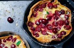 Cherry Dutch Baby tysk pannkaka för Puff på tappningpannor och mörk bakgrund, hemlagad sommarefterrätt royaltyfria foton